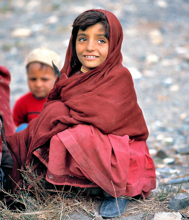 A girl in a red shawl sits with her family along the Shibar Pass in Afghanistan.