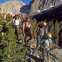 A family hikes in Big Pine Canyon, part of John Muir Wilderness in California's Sierra Nevada.  Temple Crag and Slide Mountain, part of the Palisade peaks, rises in the background.