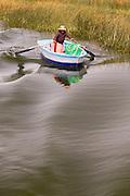 Uru woman rowing towards Floating island on Lake Titicaca, Puno, Peru, South America