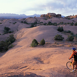 Moab, UT..Mountain biking on the Moab Slickrock Bike Trail.  Navajo Sandstone.  BLM land.