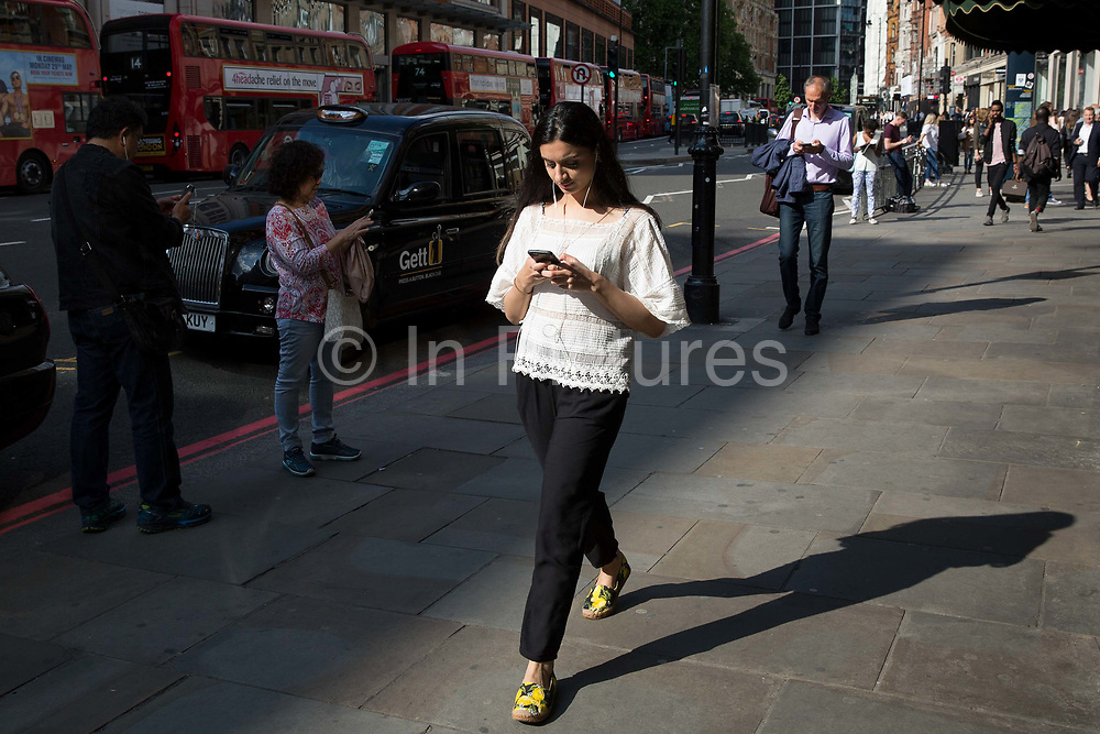 Shoppers on Brompton Road use their mobiles phones on 24th May 2017 in London, United Kingdom. Brompton Road is a street located in the southern part from Knightsbridge and in the eastern part from Brompton in the Royal Borough of Kensington and Chelsea and part of the City of Westminster in London. From the series Our Small World, an observation of our mobile phone obsessions
