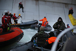 © Licensed to London News Pictures. 18/09/2013. Arctic,, UK A Russian Coast guard officer is seen pointing a gun at a Greenpeace International activist. Crew members of the Greenpeace ship Arctic Sunrise reported that a total of 11 warning shots were fired and the Coast Guard has threatened to fire at the ship itself if it does not leave the area. Five activists attempted to climb the 'Prirazlomnaya,' an oil platform operated by Russian state-owned energy giant Gazprom platform in Russias Pechora Sea. The activists are there to stop it from becoming the first to produce oil from the ice-filled waters of the Arctic.. Photo credit : Denis Sinyakov/Greenpeace/LNP