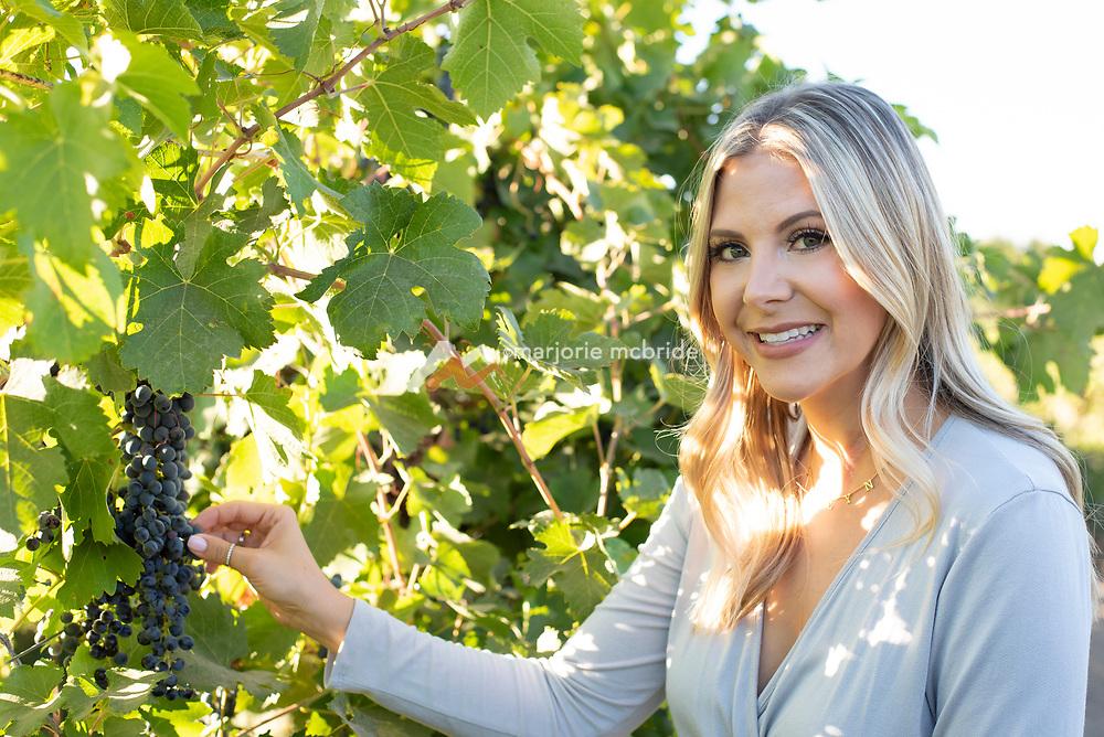 Woman picking Syrah grapes at Holeinsky Vineyard and Winery in Buhl, Idaho.