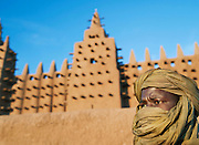 A man in headscarf outside the Great Mosque of Djenné, the worlds largest mud built structure and UNESCO heritage site, at Djenné, Mali