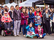 """29 APRIL 2017 - MINNEAPOLIS, MINNESOTA: People watch entertainers at the Songkran Uptown celebration. Several thousand people attended Songkran Uptown on Hennepin Ave in Minneapolis for the city's first celebration of Songkran, the traditional Thai New Year. Events included a Thai parade, a performance of the Ramakien (the Thai version of the Indian Ramayana), a """"Ladyboy"""" (drag queen) show, and Thai street food.     PHOTO BY JACK KURTZ"""