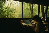 Anthropologist Cheryl Knott reviews her field notes at her open stilt house in Gunung Palung National Park.