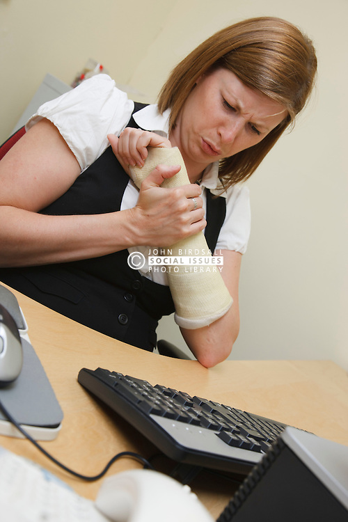 Woman at work with broken wrist feeling pain.