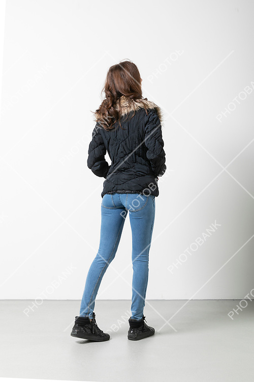 Woman seen from behind while walking with her hands in her pockets. Situation in studio on white background