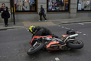 A motorcyclist struggles to his feet after being blown over by a gust of wind as Storm Doris blows across the UK and pedestrians on Fenchurch Street, brave the high winds funneled through the narrow streets, squeezed between the tall buildings of financial and insurance institutions in the City of London, on 23rd February 2017. Strong winds have led to flight cancellations and road and rail disruption across much of Britain. Thousands of homes have been left without power in Northern Ireland, Wales, Scotland and northern England.