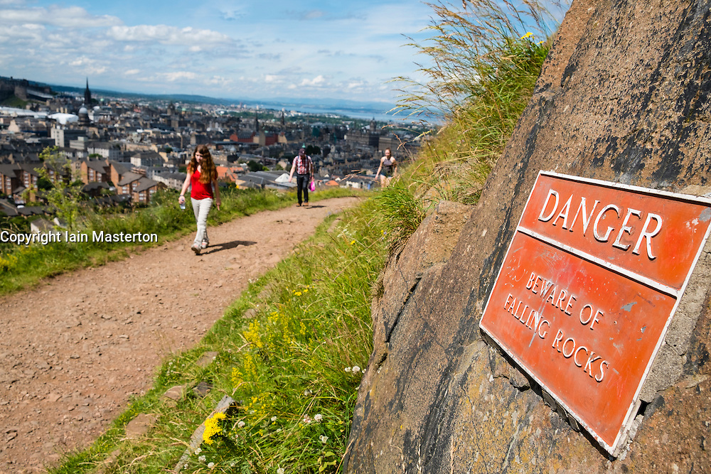 Walkers on Radical road footpath beneath Salisbury Crags high above Edinburgh in Scotland, United Kingdom
