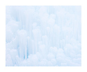 Intimate, high-key landscape image of frozen Waterfalls in winter in Banff National Park along a popular trail