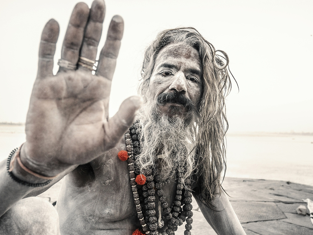 Varanasi, India - October 09, 2015 Holy man or sadhu in Varanasi India. This is the holiest city for the Jain and Hindu religion. Many sadhus cover their bodies with ashes as a sign of death and regeneration. They usually live in ashrams in the cities and practice a life of resignation of any luxuries although many accept money donation from people. Their lifes are focused on achieving mok?a, the liberation of the reincarnation cycle, through meditation and contemplation of Brahman.