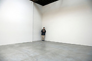 person standing in the corner of a big empty space while typing on his palm pilot