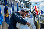 """On the dock beside USS Missouri at Pearl Harbor, """"Embracing Peace"""" (by sculptor Seward Johnson) recalls the iconic Alfred Eisenstaedt photograph, """"V-J Day in Times Square,"""" of a US Navy sailor kissing a stranger in New York City's Times Square on Victory over Japan Day (August 14, 1945). The photo was published in Life magazine with the caption, """"In New York's Times Square a white-clad girl clutches her purse and skirt as an uninhibited sailor plants his lips squarely on hers."""" Ordered in 1940 and active in June 1944, the USS Missouri (""""Mighty Mo"""") was the last battleship commissioned by the United States. She is best remembered as the site of the surrender of the Empire of Japan which ended World War II on September 2, 1945 in Tokyo Bay. In the Pacific Theater of World War II, she fought in the battles of Iwo Jima and Okinawa and shelled the Japanese home islands. She fought in the Korean War from 1950 to 1953. Decommissioned in 1955 into the United States Navy reserve fleets (the """"Mothball Fleet""""), she was reactivated and modernized in 1984 and provided fire support during Operation Desert Storm in January-February 1991. The ship was decommissioned in March 1992. In 1998, she was donated to the USS Missouri Memorial Association and became a museum at Pearl Harbor, on the island of Oahu, Hawaii, USA. For this photo's licensing options, please inquire."""
