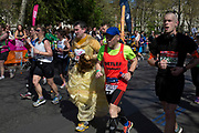 London, UK. Sunday 13th April 2014. Competitors running in the main public event of the Virgin Money London Marathon 2014. These runners take part and raise huge sums fo money for charity organisations. It is a populat traditionalso for some people to dress up in amusing costumes.