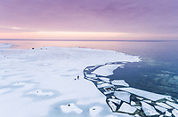 Aerial view of a man walking his dog on the frozen sea in Muraste at sunset, Estonia.
