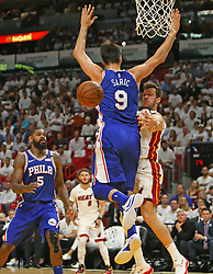 April 19, 2018 - Miami, FL, USA - The Miami Heat's Goran Dragic, right, passes aroud the Philadelphia 76ers' Dario Sarick (9) during the first quarter in Game 3 of a first-round NBA playoff series at AmericanAirlines Arena in Miami on Thursday, April 19, 2018. (Credit Image: © David Santiago/TNS via ZUMA Wire)