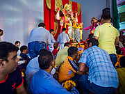 "23 SEPTEMBER 2018 - BANGKOK, THAILAND: Men approach the Ganesha deity to move it to a truck at the Ganesha Festival at Wat Dan in Bangkok. Ganesha Chaturthi also known as Vinayaka Chaturthi, is the Hindu festival celebrated on the day of the re-birth of Lord Ganesha, the son of Shiva and Parvati. The festival, also known as Ganeshotsav (""festival of Ganesha"") is observed in the Hindu calendar month of Bhaadrapada, starting on the the fourth day of the waxing moon. The festival lasts for 10 days, ending on the fourteenth day of the waxing moon. Outside India, it is celebrated widely in Nepal and by Hindus in the United States, Canada, Mauritius, Singapore, Thailand, Cambodia, and Burma.    PHOTO BY JACK KURTZ"