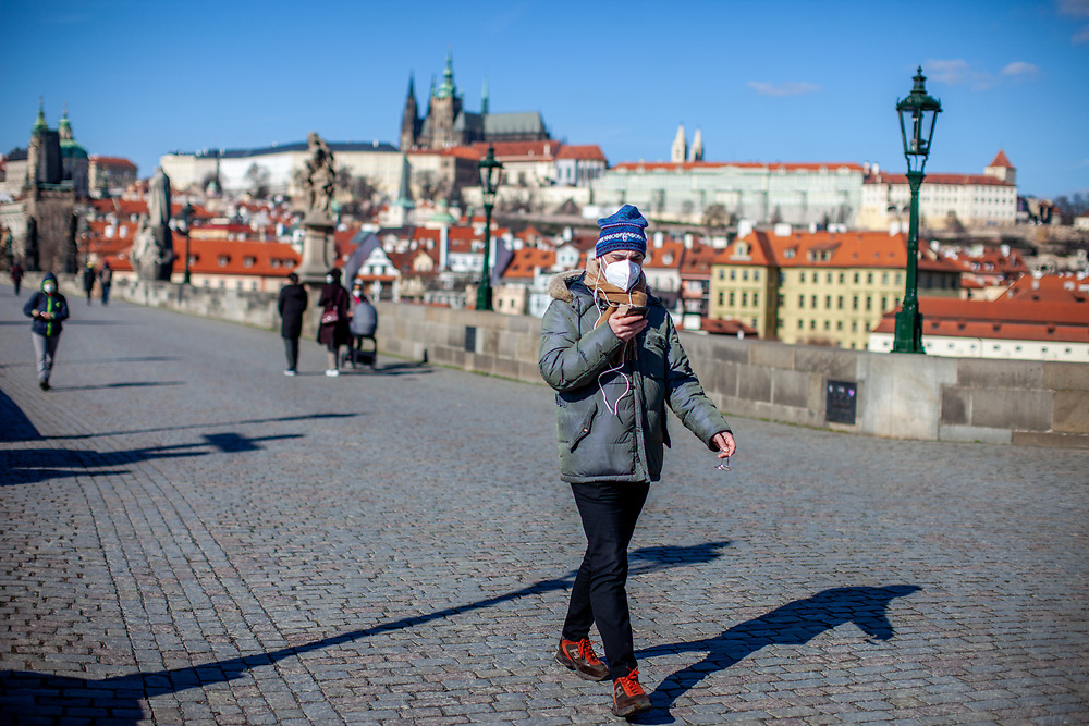 A man with face mask and smart phone walking across Charles Bridge. On March 1st, 2021 the state of emergency in the Czech Republic was reinstalled because of fast increasing numbers in infections. The lockdown was reinstated and the restriction of the free movement of people has taken effect. Currently, the country remains at the highest stage of the anti-epidemiological system and the newly imposed restriction will last at least three weeks to curb the epidemic.