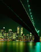 Historic night view of Manhatten and the World Trade Center prior to 9/11 viewed across the East River and framed by the Brooklyn Bridge, New York, New York.