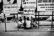 Children gather beneath signs for tour companies, taking advantage of tourism overflow from the temples at Angkor, for a game of chance, Chong Kneas, Tonle Sap, Cambodia.