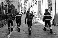 Firemen walk down a street in Milan