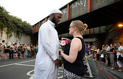 A Christian women gives a Muslim man flowers as they gather close to Finsbury Park Mosque in north London, after a van was driven into pedestrians near the north London mosque, leaving one man dead and eight injured.