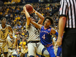 Jan 15, 2018; Morgantown, WV, USA; West Virginia Mountaineers forward Esa Ahmad (23) and Kansas Jayhawks guard Devonte' Graham (4) get tangled up in the lane during the second half at WVU Coliseum. Mandatory Credit: Ben Queen-USA TODAY Sports