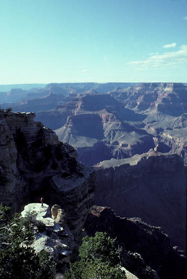 Grand Canyon National Park, Backpacker on rocky outcrop at south rim of Canyon.  Arizona.
