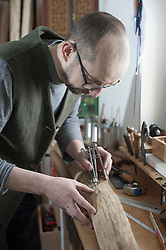 Male bow maker marking on wood with compass in workshop, Bavaria, Germany