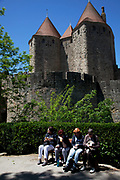 Tourists sitting having their lunch outside the walls. The Cité de Carcassonne is a medieval fortified walled town located in the French city of Carcassonne, in the department of Aude, in the region of Languedoc-Roussillon.