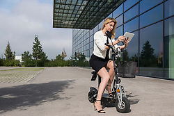 Businesswoman sitting electric powered scooter