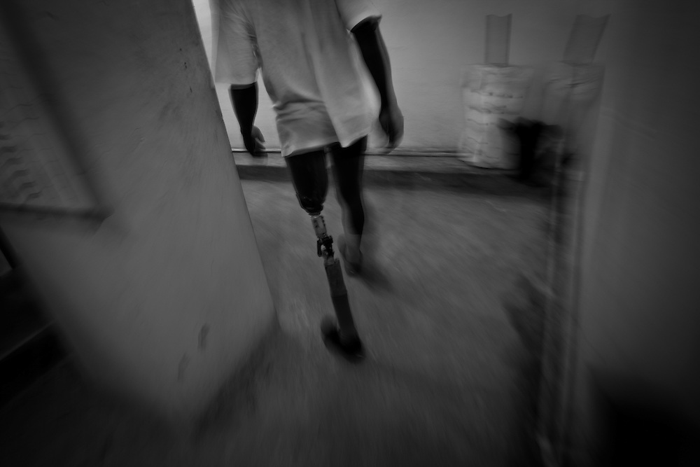 """A patient practice walking with his prosthetic leg at Healing Hands Haiti Clinic. <br /> <br /> Healing Hands Haiti (HHH) in Port Au Prince has been established for 12 years since 1999. Currently, HHH is constructing a new facility in Port Au Prince because their old clinic was destroyed from the earthquake.   HHH provides physical therapy, counseling, prosthetics, and support for free or very little cost to Haitians.  Their funding comes from private donations and organizations such as Handicap International, Mission Europeene Aide Humanitarian, International Committee of the Red Cross (ICRC), American Red Cross, Newman's Own, Direct Relief International (DRI), SOROS Open Society Foundation, and USAID which pays for employees, doctors, supplies, and facilities.  The motto of HHH is """"to serve the people of Haiti is to enable them to help themselves.""""   Thus, most of their employees are Haitians with very few foreign expats. Furthermore, HHH recruits and teaches young Haitian students prosthetic and orthotic skills and physical therapy in a specialized program that will enable them to earn a degree approved by World Health Organization."""