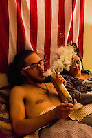 Young people smoking marijuana and relaxing at home, Aurora, Colorado USA.  Colorado was the first state to legalize the sale of marijuana for recreational use in 2014.