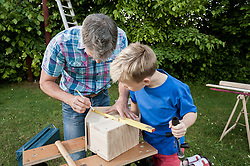 Measuring wood birdhouse building father son