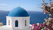 Blue dome of the Ekklisia (church) Analipsi and flowers on the Oia cliff, Santorini