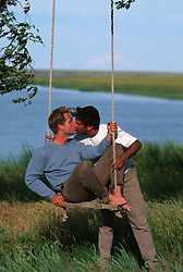 Man sitting on a rope swing being kissed by another man