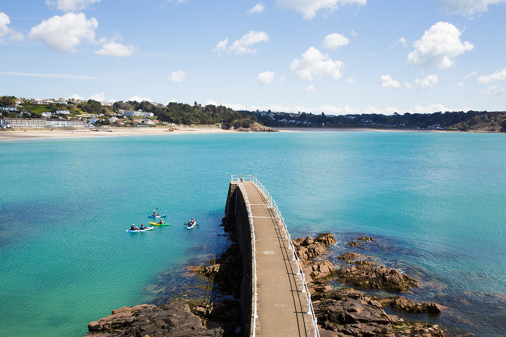 People kayaking in the turquoise water surrounding the pier at St Brelade's Bay on a summer day in Jersey