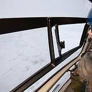 Dr. Steve Amsrup, USGS biologist, searching for polar bear tracks from a helicopter on the Beaufort Sea ice pack.  Kaktovik, Alaska.