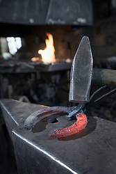 Hammering red hot horseshoe on anvil at workshop, Bavaria, Germany