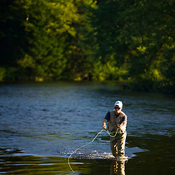 A man fly-fishing on the Connecticut River in Clarksville, New Hampshire. At confluence with Indian Stream.