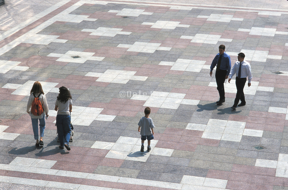 business workers and moms walking in public square