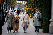 In advance of a re-opening of businesses and before a change to a Tier 2 for London during the second wave of the Coronavirus pandemic, shoppers walk past Christmas window displays outside Selfridges on Oxford Street, on 30th November 2020, in London, England. Retailers will once again be open for Christmas business on 3rd December.