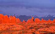 Fiery sunset casts a wam glow on The Windows, while clouds cloak the La Sal mountains in blue shadows, Arches  National Park, near Moab, Utah