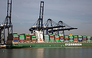 Evergreen container ship and cranes in the Port of Felistowe, Britain's busiest container port, pictured from across the River Orwell at Shotley, Sufolk, England