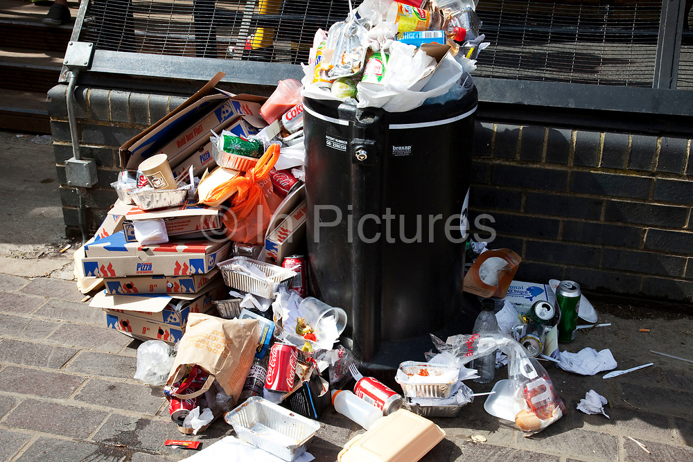 Litter overflows a bin at Camden Lock at the market in North London. Rubbish due to crowds builds throughout the day until eventually the bins cannot cope with the amount of trash.Pizza boxes, cups, cans, plastic, cardboard.