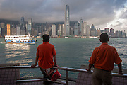 Two workers wait for a boat that will pick them up for their days work. At approximately 6am workers start to gather here near the Star Ferry terminal in Kowloon. Hong Kong skyline, dominated by the Bank of China building towers over Hong Kong Harbour in the morning light.