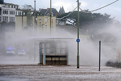 © Licensed to London News Pictures. 03/02/2014. Exmouth, UK . Police close the road. Seawater floods the seafront in Exmouth Devon.The water breached defences and flooded Morton Road, St Andrews Roads, Victoria Road and some of the other surrounding streets. Police closed the road to vehicles. Officials were seen delivering sandbags to the local residents. . Photo credit : Russ Nolan/LNP