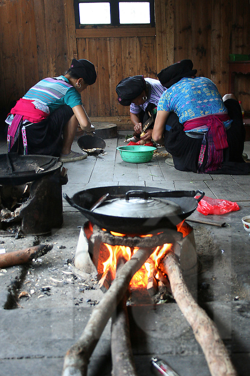 Ethnic women cook.  fireplace with a pot in foreground. Area of Ping'an, Guangxi, China, Asia