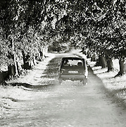 Small car driving down a dusty road in Herthaburg, near Sassnitz on the island of Rugen, northern Germany